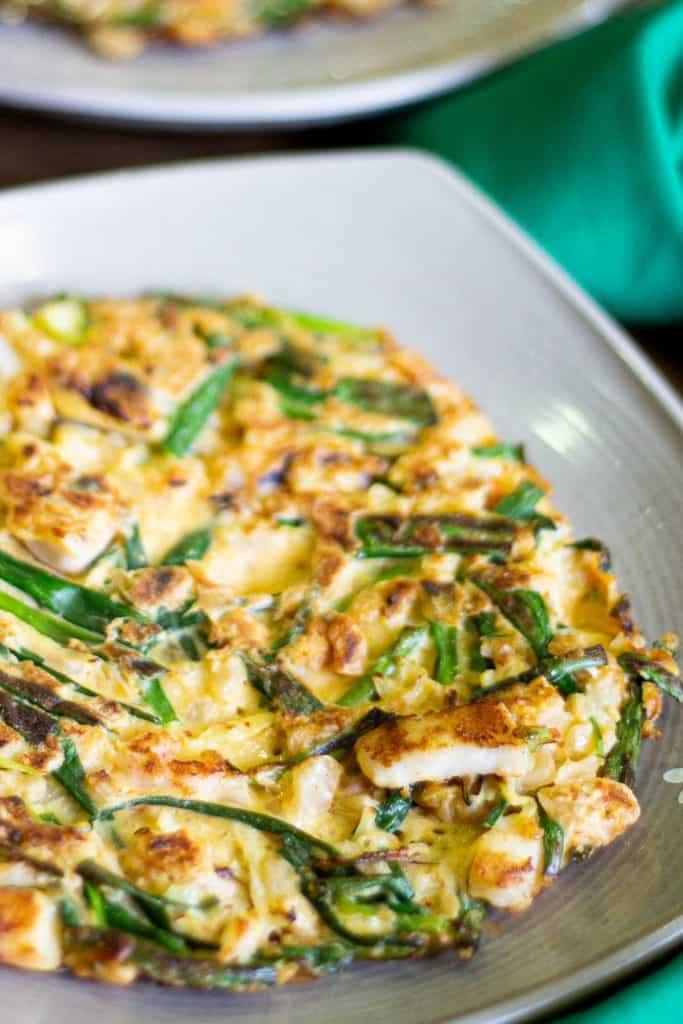 A crispy fried Korean kimchi and seafood pancake on a plate.