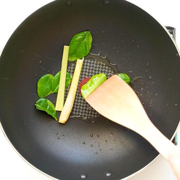 Stir frying kaffir lime leaves and fresh lemongrass stalks in a wok.