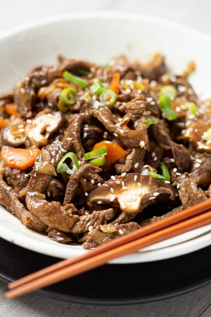 Beef bulgogi cooked with shiitake mushrooms in a bowl next to wooden chopsticks.