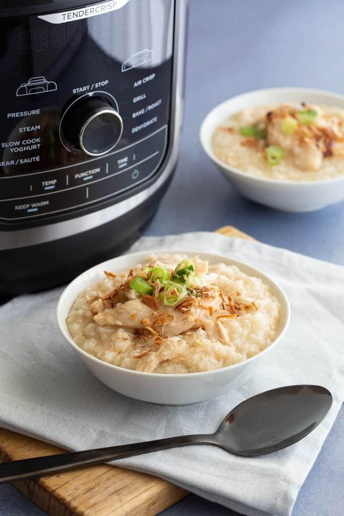 Ninja Foodi multi-cooker alongside bowls of chicken congee (chao ga).