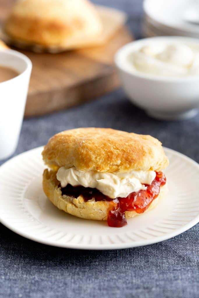 Plain scone filled with jam and cream on a white plate.