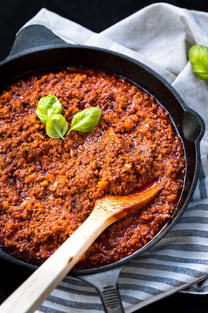Italian ragu in a large pan with spoon.