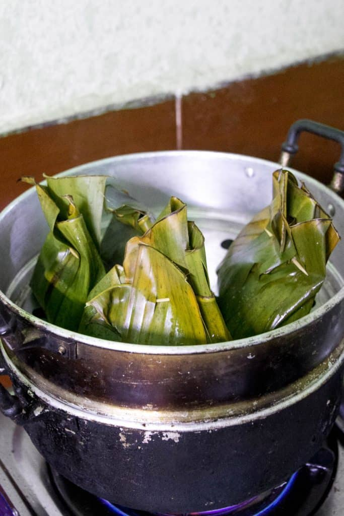 Uncooked fish in banana leaf wrappers sitting in a steamer ready to be cooked.