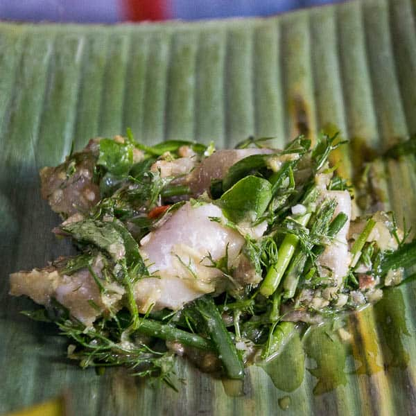 Diced fish and herbs placed onto a banana leaf.