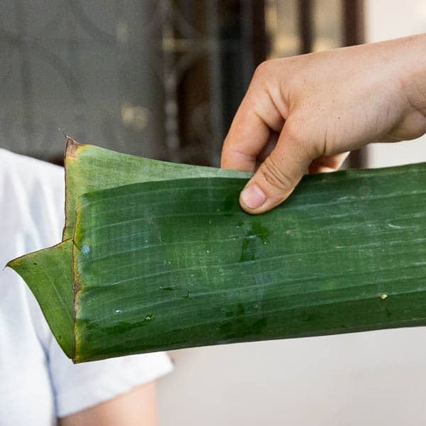 Folding the bottom and top sides of the banana leaf over the fish filling.