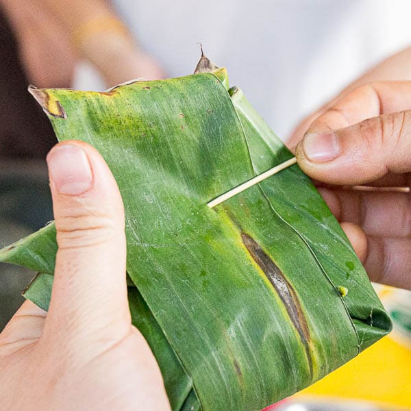 Threading a bamboo skewer through the banana leaves to seal the fish parcel.