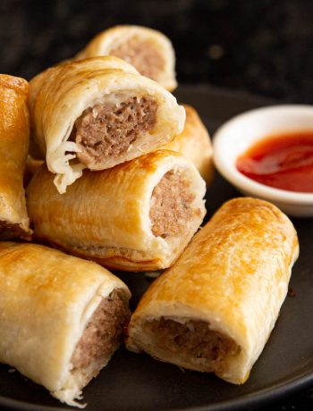 Close up of sausage rolls with tomato sauce.