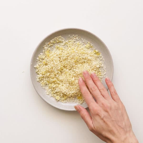 Adding olive oil to panko crumbs.