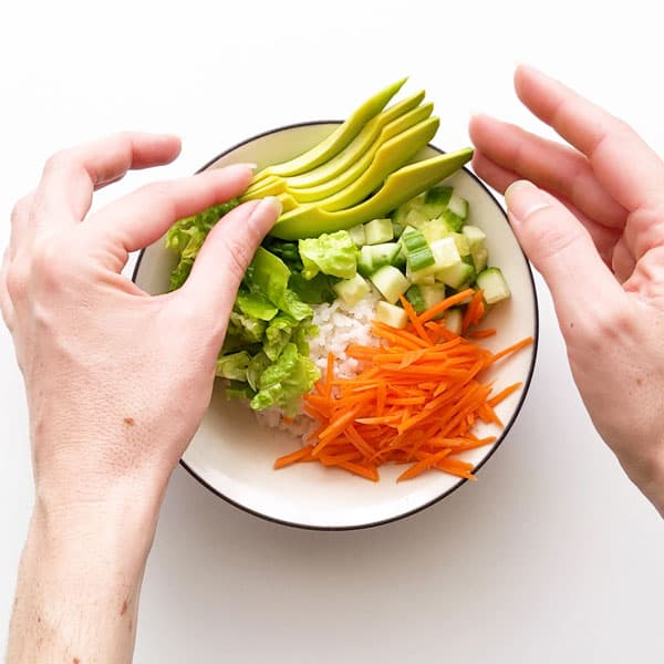 Assembling the sushi bowl ingredients - rice, cucumber, lettuce, carrot and avocado.