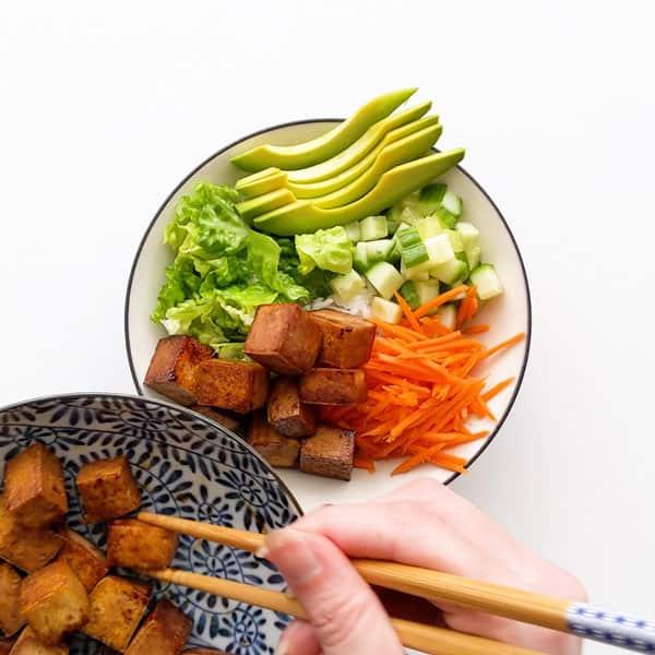 Adding teriyaki tofu on top of the rice and vegetables.