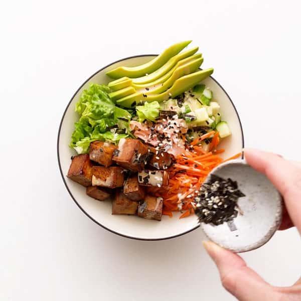Seasoning the sushi bowl with furikake.