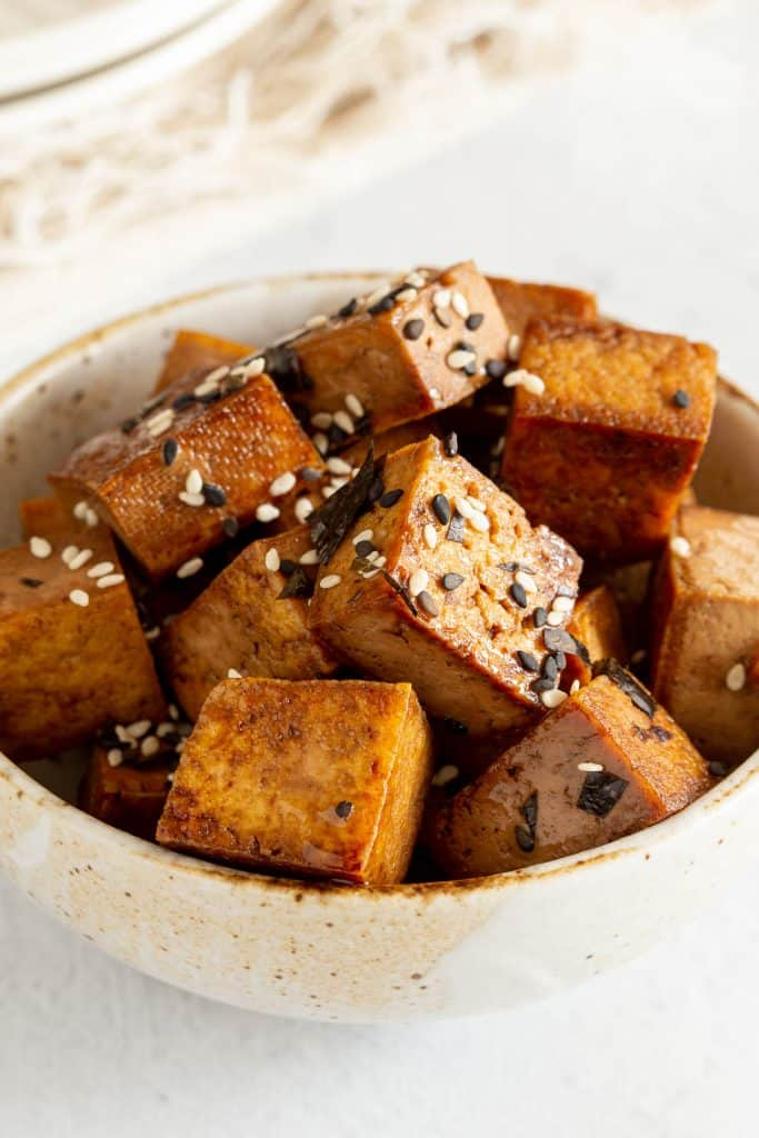 A bowl of tofu stir fried in teriyaki sauce.