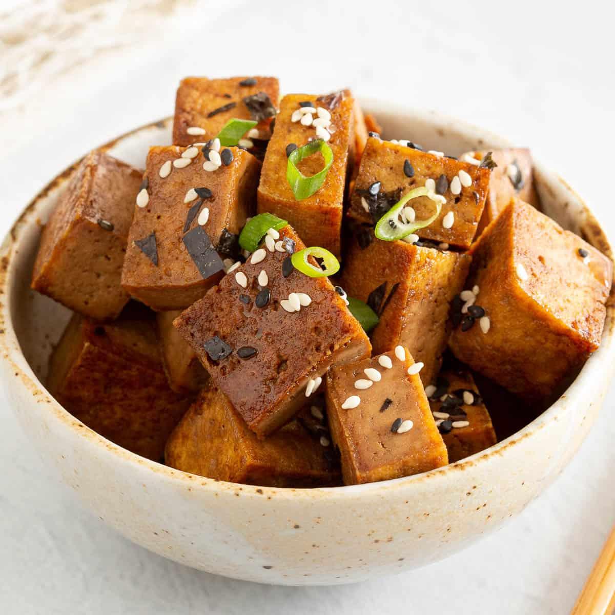 Close up shot of teriyaki tofu garnished with furikake and spring onion.