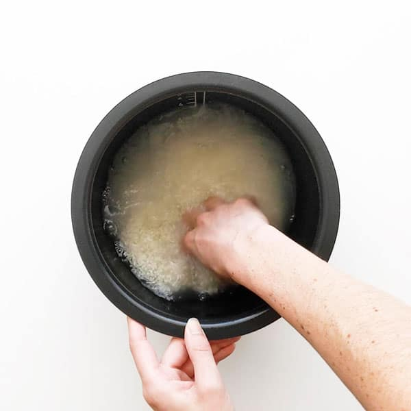 Washing rice in water before cooking.