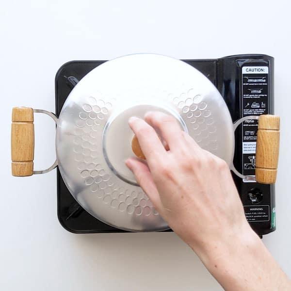 Placing lid on the saucepan.