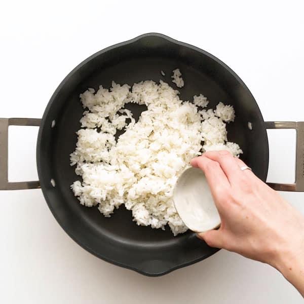 Pouring seasoned sushi vinegar over rice.