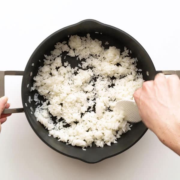 Folding the sushi vinegar through the sushi rice with a rice paddle.