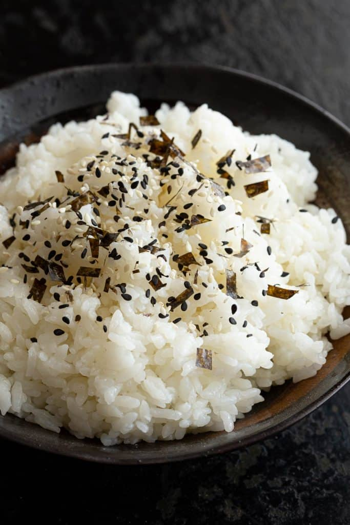 A bowl of cooked rice sprinkled with furikake rice seasoning.