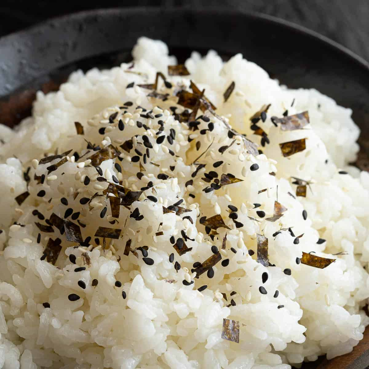 Close up shot of nori komi furikake sprinkled over sushi rice.
