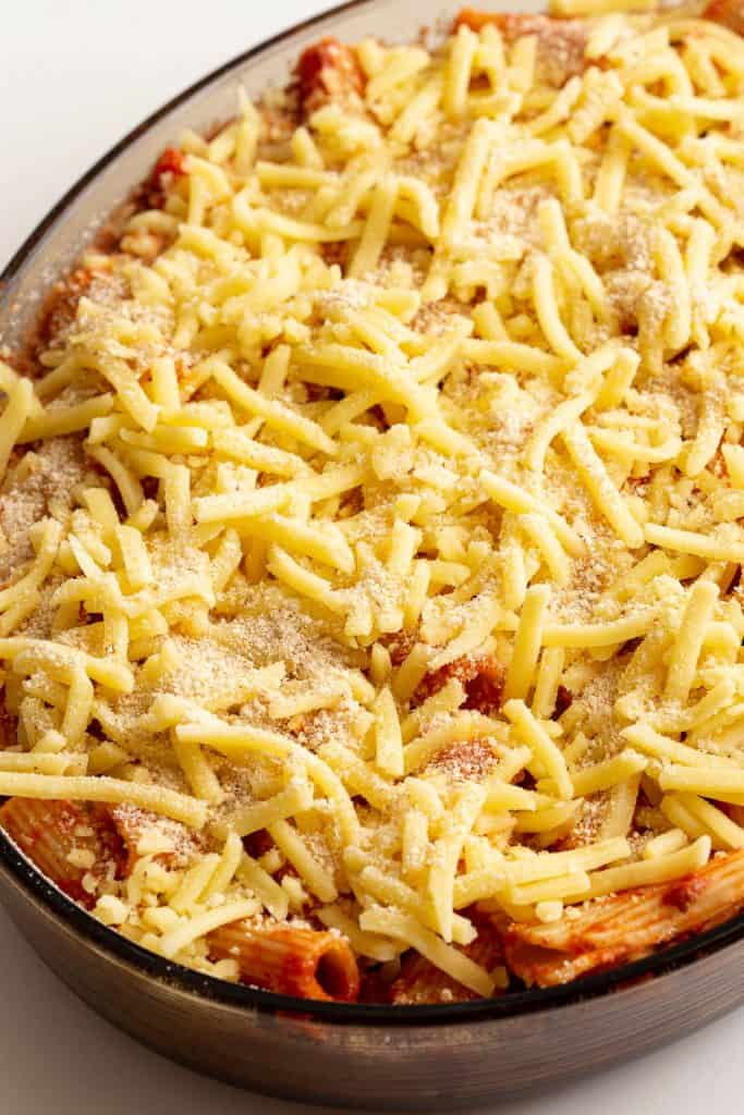 Cooked pasta and sauce covered with mozzarella and bread crumbs, ready to be baked.