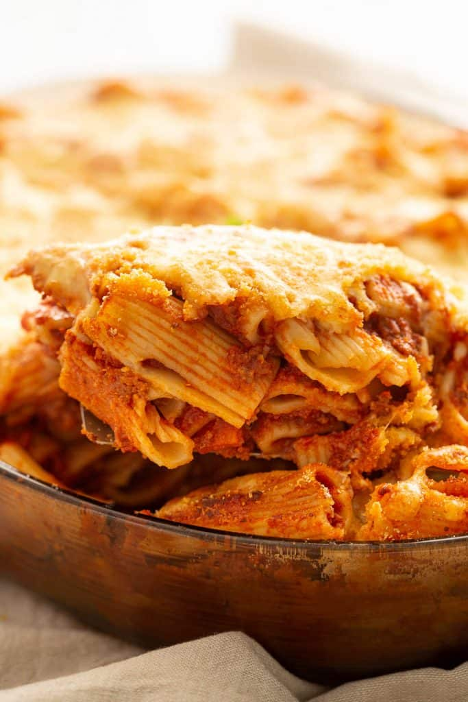 Serving a slice of Italian pasta bake from the baking dish.