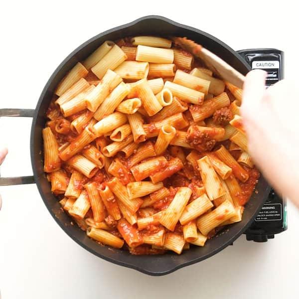 Mixing pasta through the ragu meat sauce.