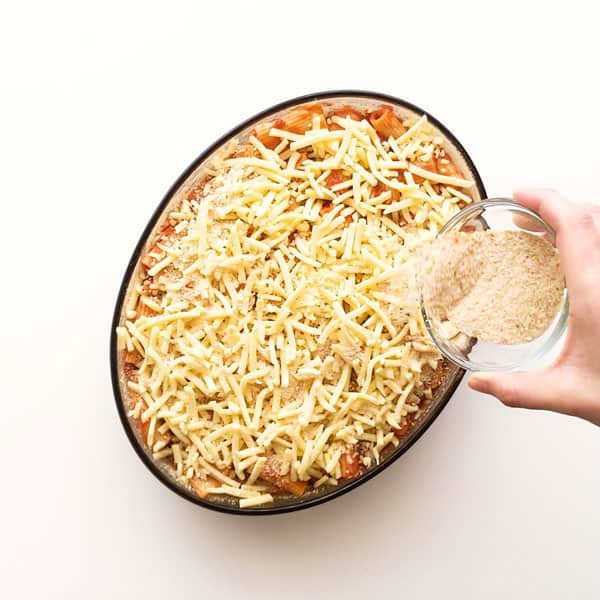 Sprinkling cheese and bread crumbs over the prepared pasta al forno.