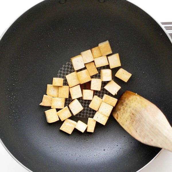 Frying tofu in vegetable oil until brown.