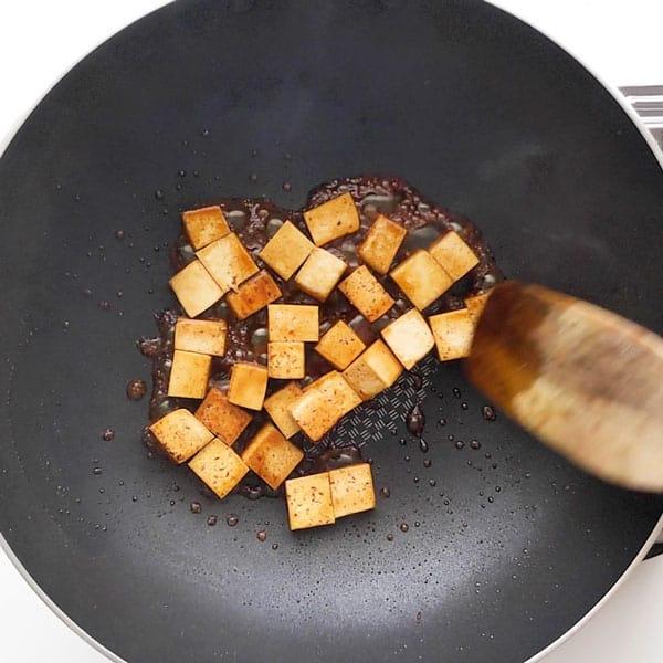 Frying the tofu in teriyaki sauce.
