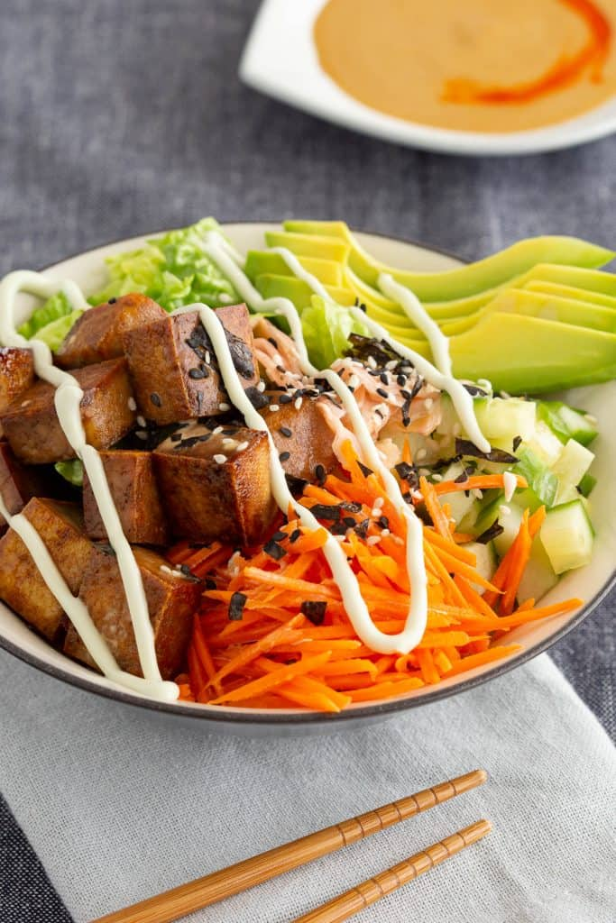A colourful sushi bowl with tofu and vegetables, next to a bowl of sauce.