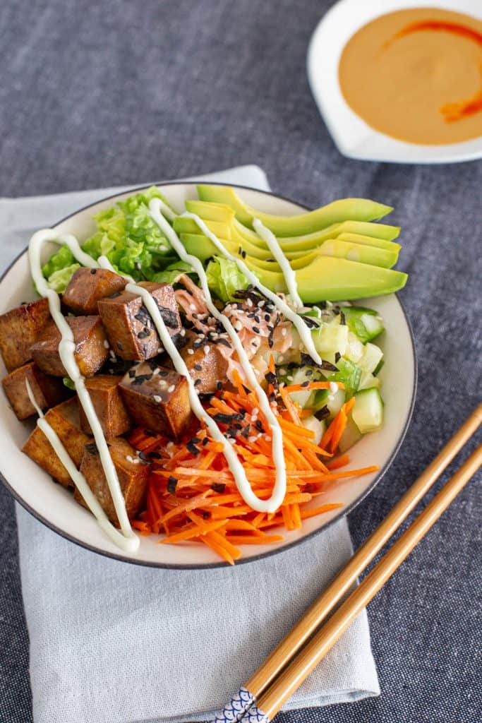 A deconstructed sushi bowl next to chopsticks and a bowl of sauce.