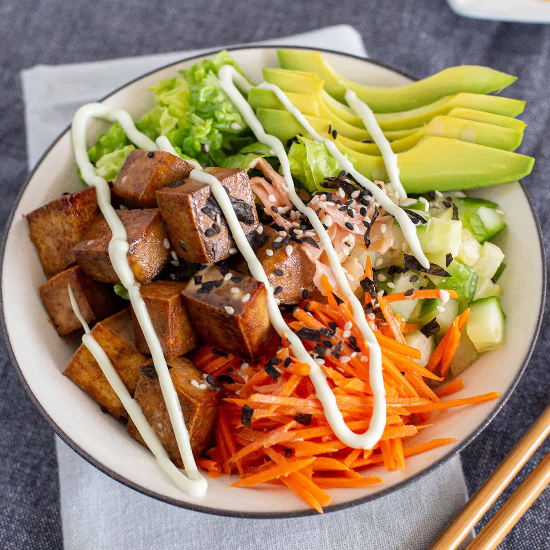 Close up shot of sushi bowl with teriyaki tofu and vegetables.