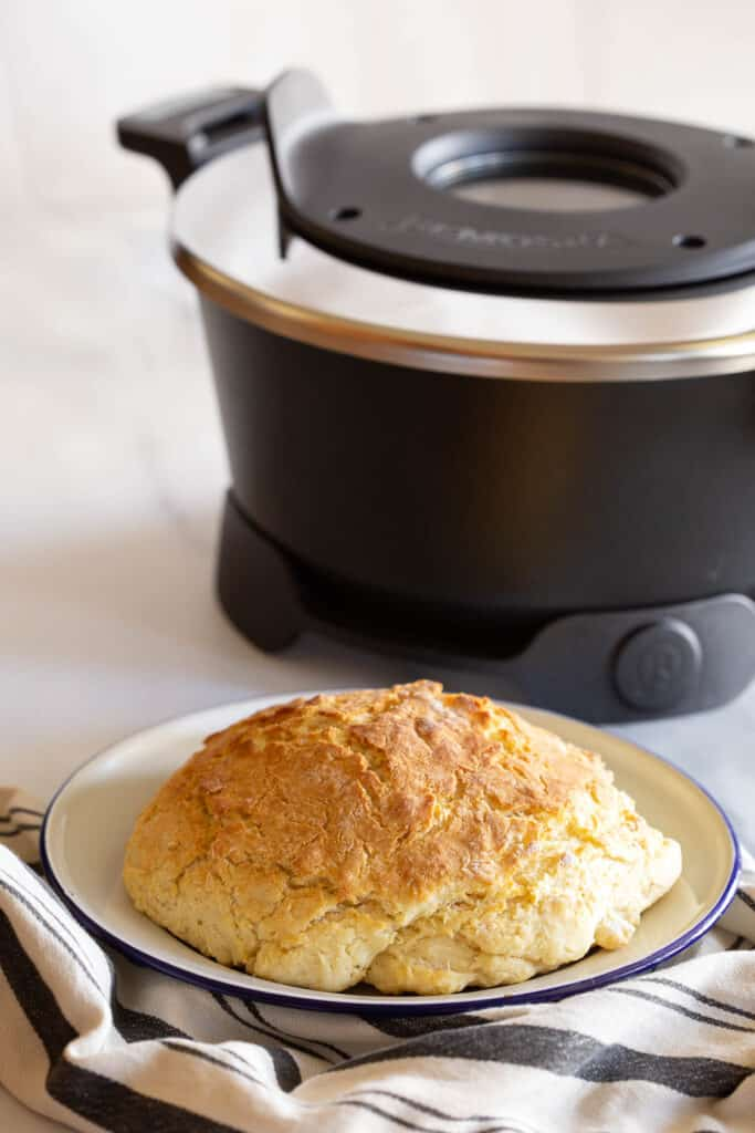 Damper bread with Remoska cooker in background.