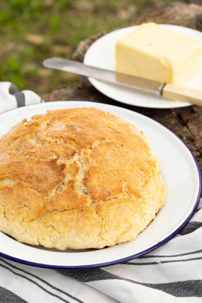 Fresh loaf of damper bread with a slab of butter.