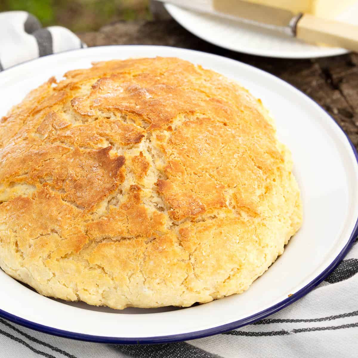 Fresh damper bread on a blue and white plate.