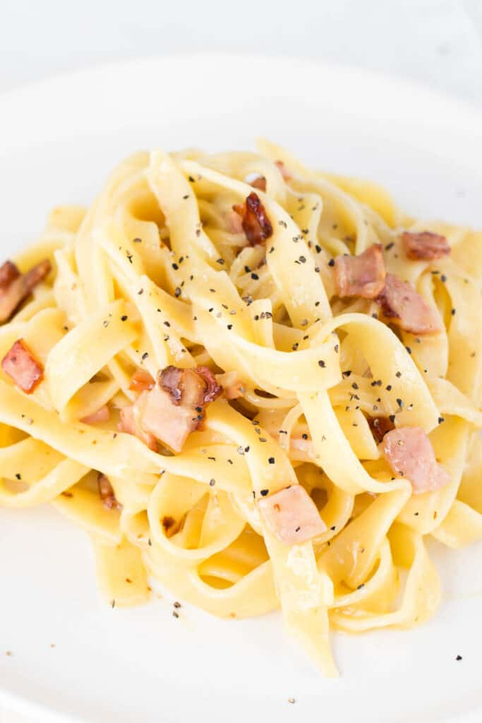 A bowl of carbonara pasta garnished with cracked black pepper.