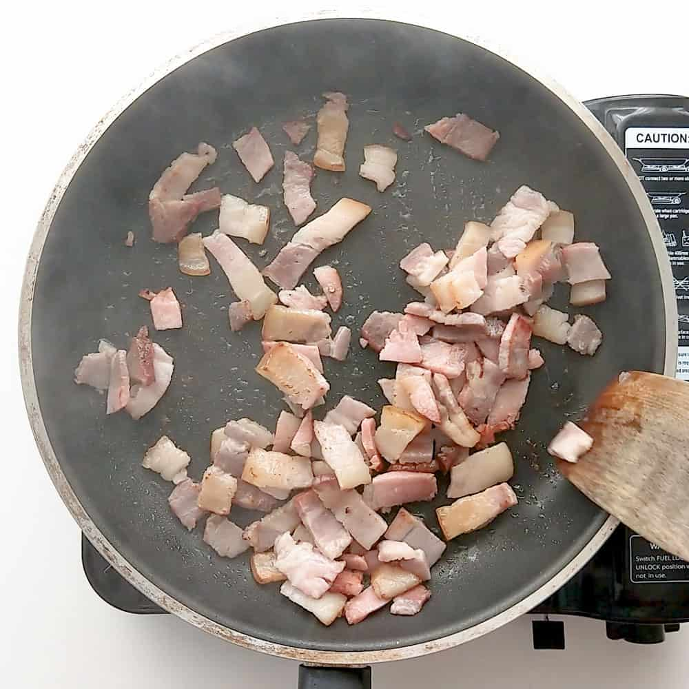 Cooking pancetta in a frying pan.