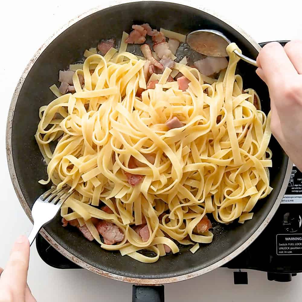 Tossing freshly cooked pasta with the cooked pancetta.