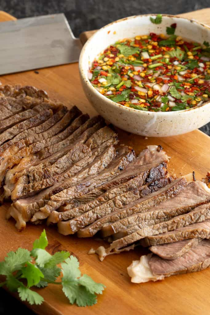 Sliced crying tiger beef on a wooden board with coriander and dipping sauce.