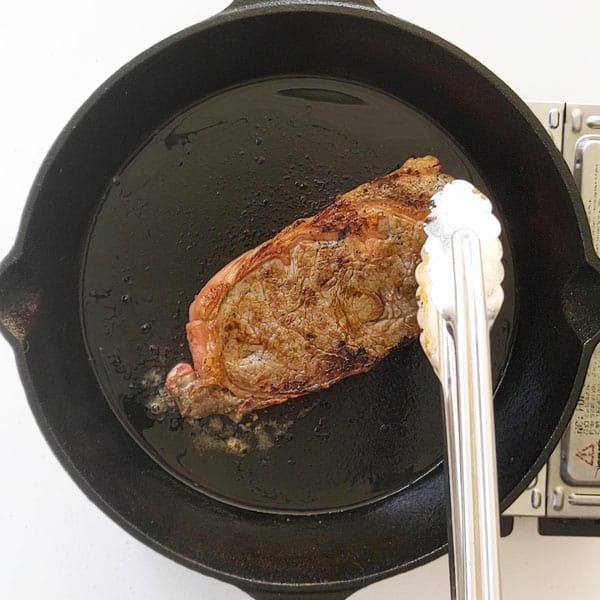 Frying a sirloin steak on a pan.