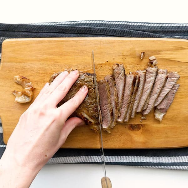 Thinly slicing the crying tiger steak.