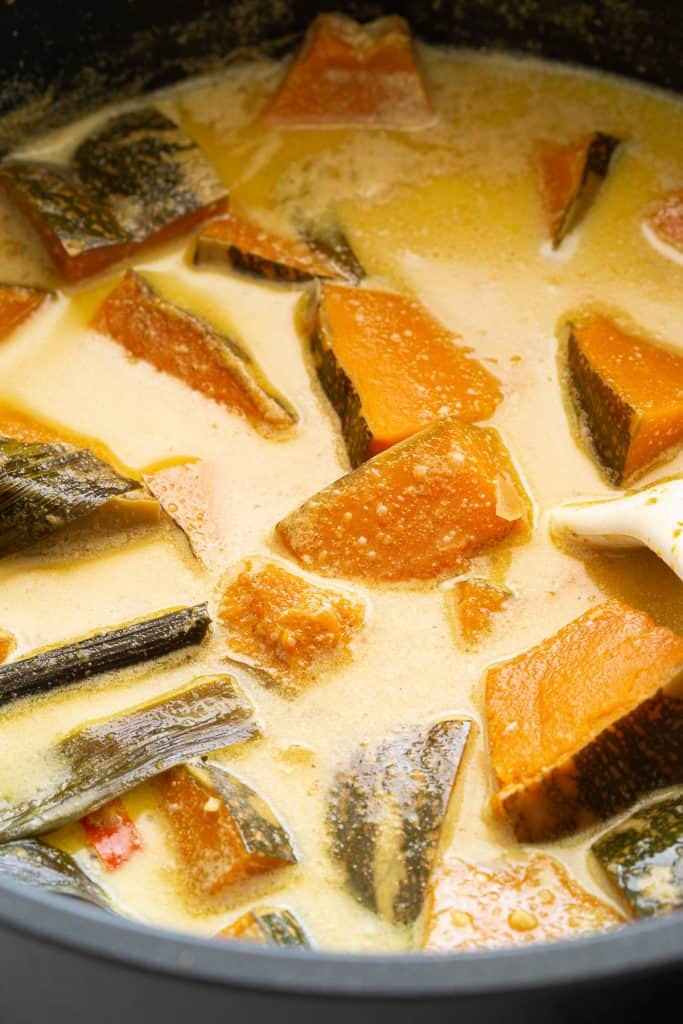 Close up of pot with pumpkin pieces in creamy coconut curry.