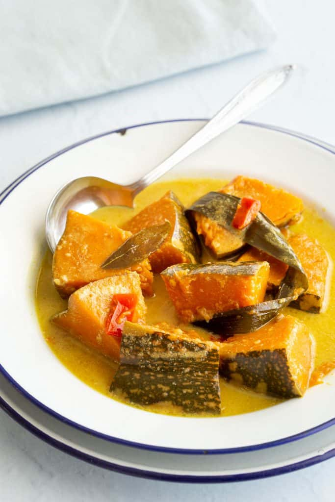 White bowl with spicy wattakka kalu pol curry.