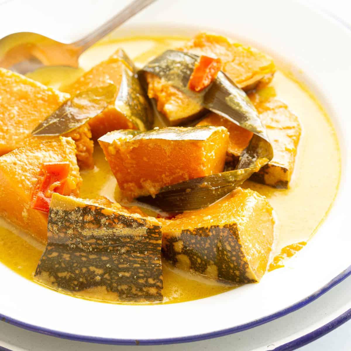 White bowl full of creamy pumpkin curry.