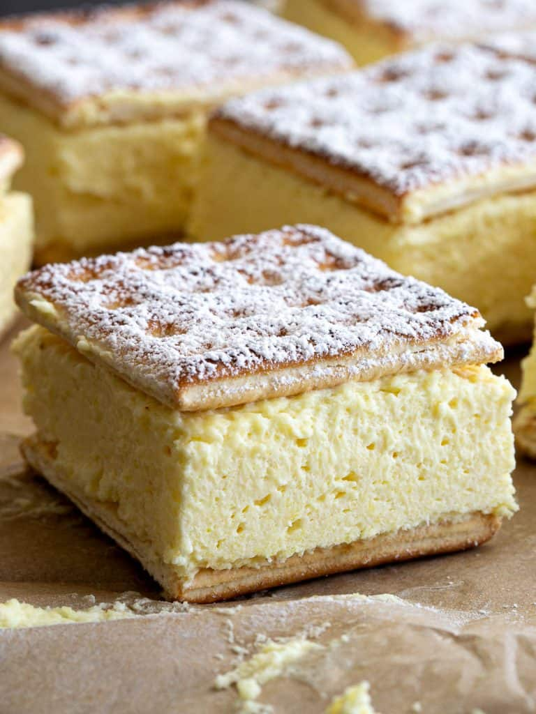 The finished vanilla slice made with lattice biscuits and instant dessert mix, sprinkled with icing sugar.