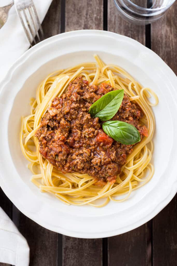Bowl of pasta topped with Bolognese sauce and basil.