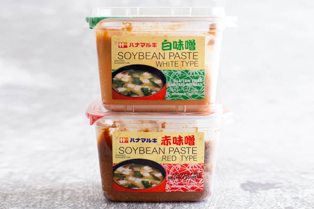 Two tubs of miso paste stacked on top of each other.