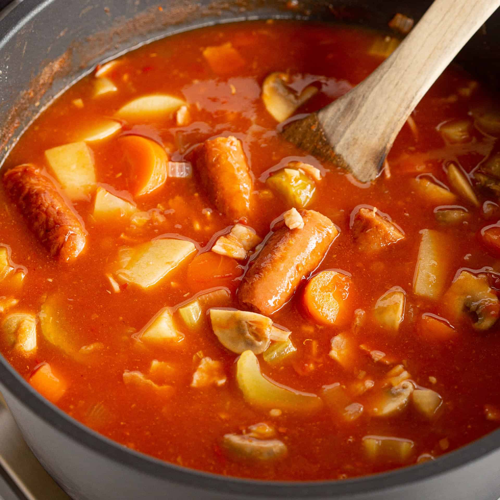 Sausage and bean casserole in Remoska with wooden ladle.
