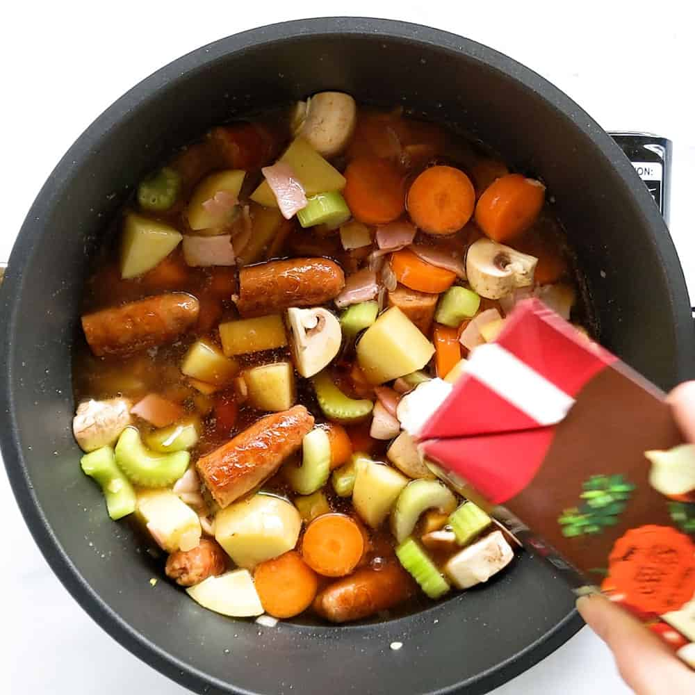 Pouring beef stock over vegetables.