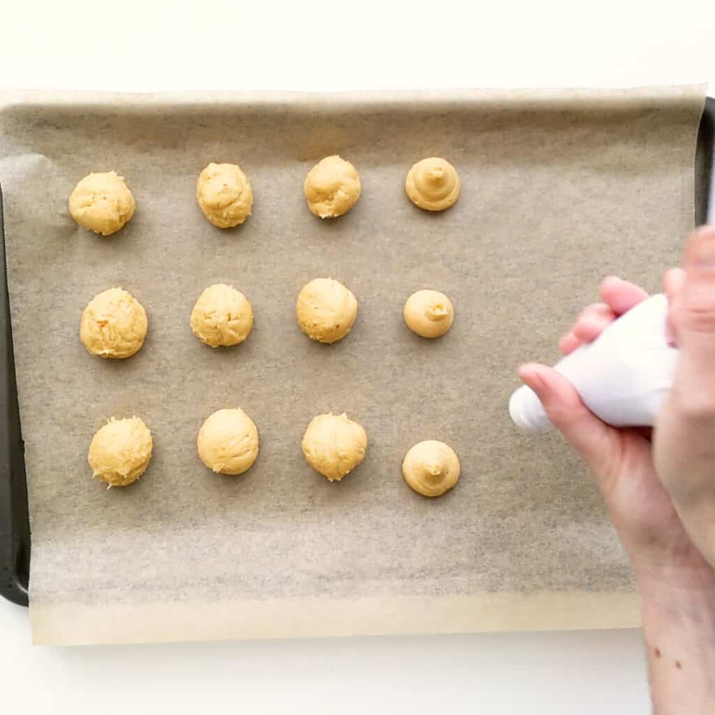 Piping out ginger kisses onto tray.